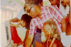 Prof. Samaranayajke, then Chairman, CINTEC demonstrating computer use to the Veddha Chief Tissahamy at Dambane, the Veddha village in 1990 using the equipment of the CINTEC mobile Computer Lab. Also in the picture are his sons Nayana and Samitha and Present Veddha Chief Vannialage Aththo. Son of Tissahamy.
